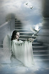 A young angelic female wearing white robes kneeling beside a stone stairway releasing white doves