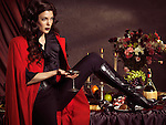 High fashion photo of a beautiful woman in red coat sitting on a festive table with a glass of wine in her hand