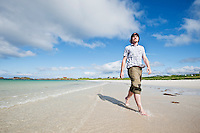 Person walks along scenic white sand beach, Gimsøya, Lofoten islands, Norway