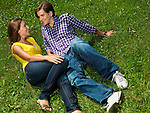 Young happy couple in their early thirties lying on grass in a park
