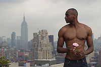 shirtless African American man holding a pink rose while standing on a rooftop overlooking New York City