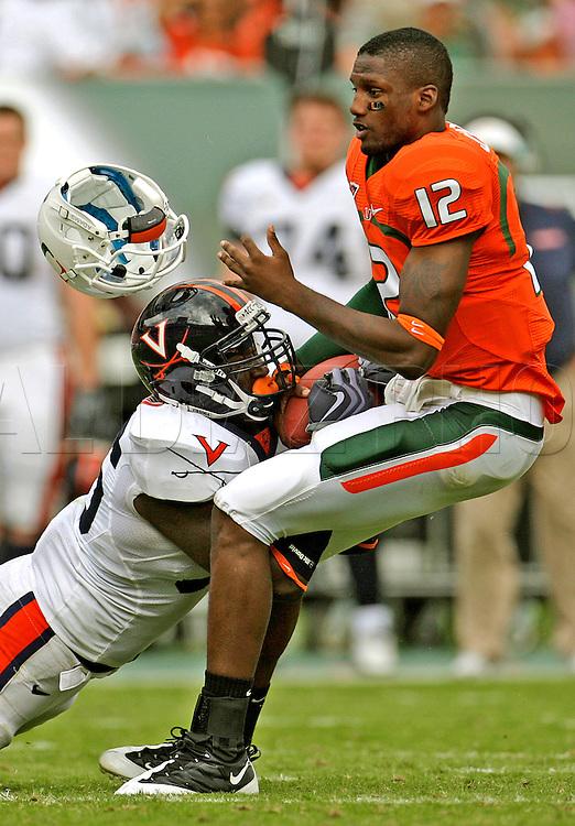 The University of Miami vs Virginia Cavaliers at Land Shark Stadium on Saturday November 7...Virginia linebacker Cam Johnson (56) face masksand rips the helmet off Miami's quarterback Jacory Harris (12) in the third quarter.