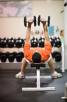 young man lifts barbell weights to strengthen his chest at a athletic club