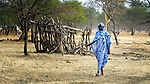 A woman walks past the remains of a destroyed house in Mijak, a village in the contested Abyei region from which residents fled in 2011 after an attack by soldiers and militias from the northern Republic of Sudan. Although the 2005 Comprehensive Peace Agreement called for residents of Abyei--which sits on the border between Sudan and South Sudan--to hold a referendum on whether they wanted to align with the north or the newly independent South Sudan, the government in Khartoum and northern-backed Misseriya nomads, excluded from voting as they only live part of the year in Abyei, blocked the vote and attacked the majority Dinka Ngok population. The African Union has proposed a new peace plan, including a referendum to be held in October 2013, but it has been rejected by the Misseriya and Khartoum. The Catholic parish of Abyei, with support from Caritas South Sudan and other international church partners, has maintained its pastoral presence among the displaced and assisted them with food, shelter, and other relief supplies. A handful of residents have returned to Mijak, yet most remain displaced in nearby towns, waiting a definitive peace deal before returning home.