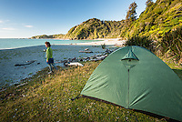 Woman camping at Smoothwater Bay near Jackson Bay, South Westland, West Coast, South Island, World Heritage Area, New Zealand