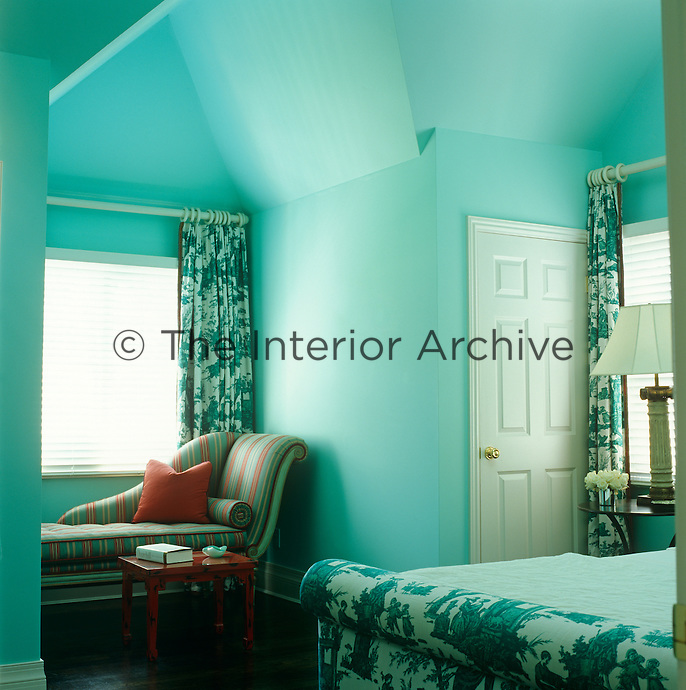 In this predominantly turquoise bedroom a small Chinese lacquer table srikes just the right note of contrast picking out the red stripe in the upholstery of a nearby chaise longue