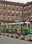 A grandfather and grandson sit and wait at a tram stop in front of a green tram in Turin, Italy