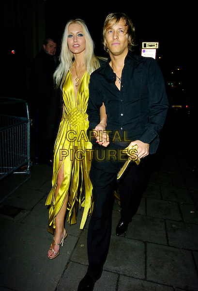 EMMA NOBLE & RICK PARFITT JR..At Andy & Patti Wong's Chinese New Year Party,.Madame Tussards,London, England, January 27th 2007..full length yellow satin silk dress shredded low cut holding hands.CAP/CAN.©Can Nguyen/Capital Pictures