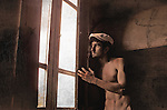A naked young man wearing a cap standing in a room looking out of a large window