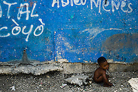 A Haitian baby plays in the slum of Cité Soleil, Port-au-Prince, Haiti, 24 July 2008. Cité Soleil is considered one of the worst slums in the Americas, most of its 300.000 residents live in extreme poverty. Children and single mothers predominate in the population. Social and living conditions in the slum are a human tragedy. There is no running water, no sewers and no electricity. Public services virtually do not exist - there are no stores, no hospitals or schools, no urban infrastructure. In spite of this fact, a rent must be payed even in all shacks made from rusty metal sheets. Infectious diseases are widely spread as garbage disposal does not exist in Cité Soleil. Violence is common, armed gangs operate throughout the slum.