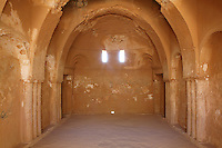Qasr Kharana, desert castle, Jordan. This room has a vaulted ceiling, pilasters, small slit windows and shows a Sassanid influence. This building was built c. 710 in the early Umayyad period under the Caliph Walid I although its purpose is unknown. It did not have a military function. It is a square building with small projecting corner turrets and a projecting round entrance seen here on the South side. It has 60 rooms inside over two floors around a central courtyard where rain is collected. The small slit windows are for light and ventilation. It fell out of use and was damaged by several earthquakes before being rediscovered in 1901 and restored in the 1970s. Picture by Manuel Cohen