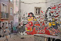 Fado Vadio graffiti mural in the Escadinhas de Sao Cristovao, Alfama, Lisbon, Portugal. The mural celebrates traditional fado folk music, which originated from here. It was created by the Movimento dos Amigos de Sao Cristovao, a local community group, which worked with artists to create the graffiti mural. The work contains portraits of fado singers such as Maria Severa and Fernando Mauricio, song lyrics and views of the neighbourhood. Picture by Manuel Cohen
