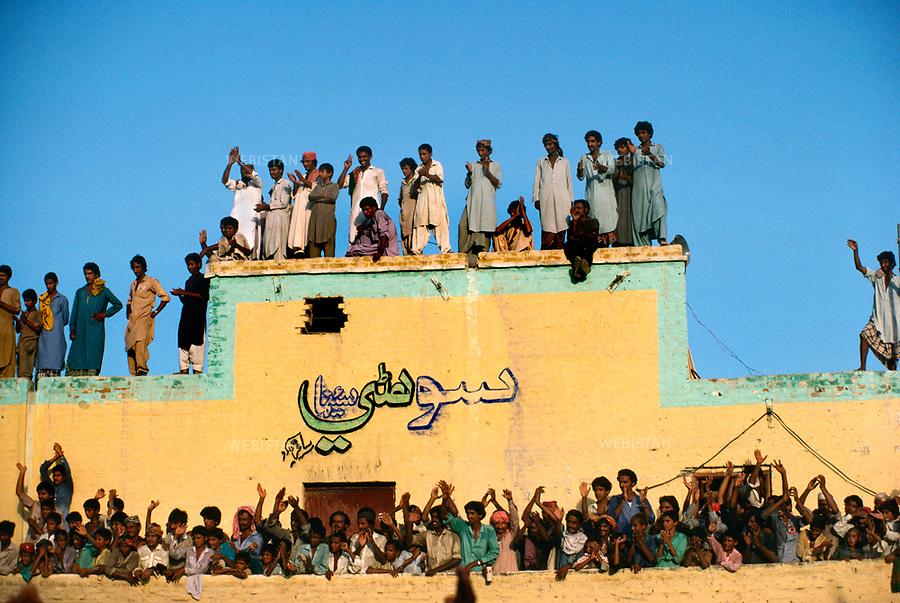 Pakistan. 1986. Benazir Bhutto's elections ..campaign. Supporters gathered in a Baluchistan village for the passage of Benazir Bhutto..... Pakistan. 1986. Campagne electorale de Benazir Bhutto. Supporters rassembles dans un village du Baluschistan pour voir le passage de Benazir Bhutto...