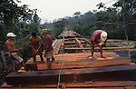 YANOMAMI INDIANS. South America, Brazil, Amazon. Bridge building development access to Indian lands. Yanomami indians, a primitive tribe, living in the tropical rainforest, in communal traditional molaca dwellings. They are huntergatherers passing on their traditions and skills  from generation to generation. They are the guardians of their forest and its fragile ecosystem. Their lifestyle and their lands diminish every year in the face of encroaching deforestation, forest fires, campesinos who slash and burn primary rainforest, from cattle ranching, commercial plantations, gold and diamond mines.