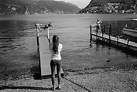 Switzerland. Canton Ticino. Lugano. Tourists on holiday on Lake Lugano. A woman takes a picture of her two friends standing in balance on a wharf pier's pillars. An elderly man takes a snapshot from another pier. 24.05.2016 © 2016 Didier Ruef