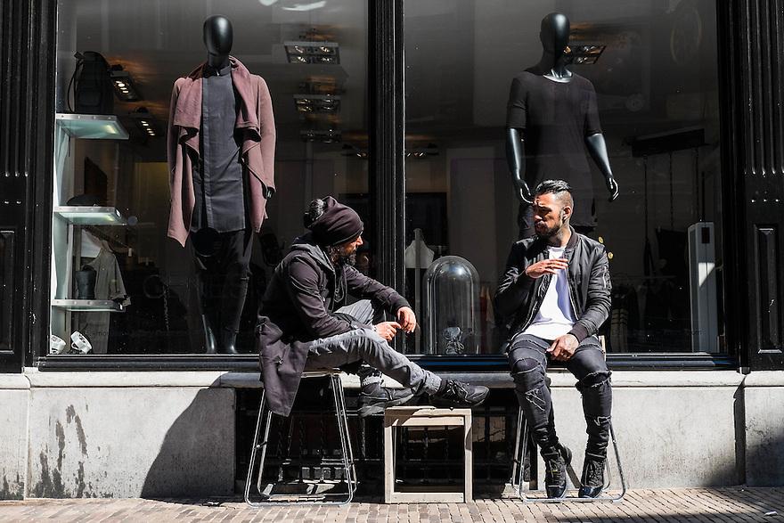 Nederland, Utrecht, 18 april 2015<br /> Twee modieus geklede mannen zitten voor hun winkel te praten. Het is rustig, er zijn geen klanten ondanks het mooie weer.<br /> Foto: Michiel Wijnbergh