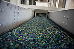 "A picture taken on November 3, 2015 shows shredded plastic waste collected in the sea by fishermen on a conveyer belt at a plastic processing plant in Chiva, near Valencia . Ecoalf, a Spanish Madrid-based firm founded in 2010, has already launched ""a new generation"" of clothes and accessories made from plastic bottles, old fishing nets and used tires found on land. © Pedro ARMESTRE"