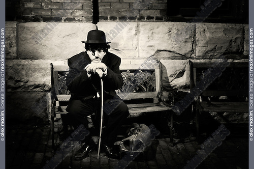 Charlie Chaplin mime Businessman in black suit down-and-out sitting on a bench in the street alone with a dramatic expression. Artistic humorous concept. Performing artist Peter Jarvis.