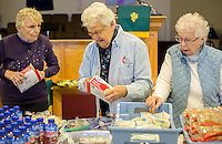 STAFF PHOTO JASON IVESTER --11/13/2014--<br /> Volunteers Laurie Drews (from left), Patsy White and Virginia Narramore (cq) sort food to distribute to visitors to the food pantry on Thursday, Nov. 13, 2014, inside Grace United Methodist Church in Rogers.