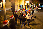 The Santa hats of the Mountain View High School madrigals are a colorful addition to State Street.