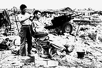 Pfc. Troy Dixon, Leadhill, Ark., uses a Japanese barber chair to cut the hair of Sgt. John Anderson, Anita, Pa.  Both men are members of the 363rd F.A. Bn., located near Shuri, Okinawa, June 10, 1945.  Hendrickson.  (Army)<br /> NARA FILE #:  111-SC-208582<br /> WAR &amp; CONFLICT BOOK #:  928
