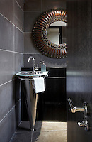 A view through an open door to a grey tiled bathroom. A conical shaped washbasin is set in the corner of the room.
