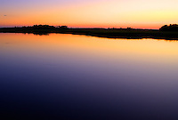 The simple beauty of sunset on water, marsh grasses and sky captured by an HDR image