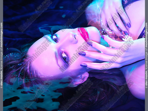 Beauty treatment conceptual photo. Woman lying in water wearing makeup and nail polish under colored purple blue light. Closeup of face.