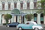 Havana, Cuba; a classic blue and white 1950 Oldsmobile driving along the Paseo de Marti past the Saratoga Hotel