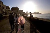 Family members stroll Havana's crumbling Malecón.