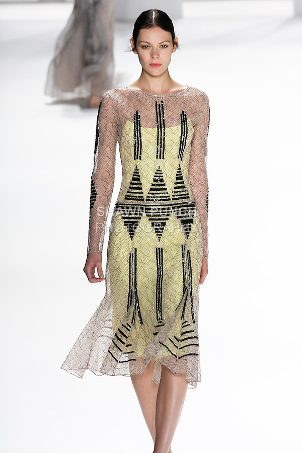 Kinga Rajzak walks the runway in a nude and black geometric lace long sleeve dress with linear bead embroidery for the Carolina Herrera Spring 2012 fashion show, during Mercedes-Benz Fashion Week Spring 2012.