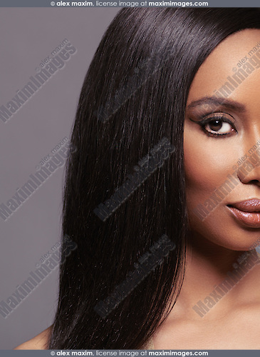 Artistic closeup beauty portrait of young african american woman face with long straight hair on gray background