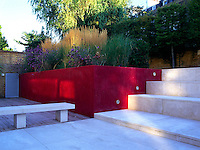 Red Plastered terraced bed with white sandstone paving and hardwood Cedar decking. Limestone bench and steps leading to back of garden lined in pleached Hornbeams