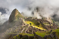 Morning fog and clouds reveal Machu Picchu, the ancient &quot;lost city of the Incas&quot;, 1400 CA, 2400 meters.  Discovered by Hiram Bingham in 1911. One of Peru's top tourist destinations.