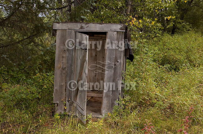 Outhouse and cabins in gold-rush era ghost town along the Dalton Trail near Haines, Alaska