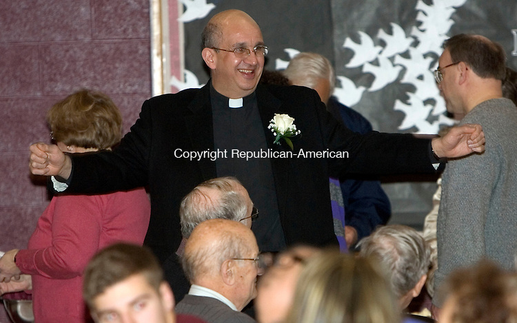 """TORRINGTON, CT. 12 January 2013-011313SV02- Rev. Christopher Tiano jokes with some parishioners at an open House at St. Peter-St. Francis School in Torrington Sunday. Father Tiano was named """"most distinguished pastor."""".Steven Valenti Republican-American"""