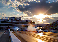 Sep 16, 2016; Concord, NC, USA; Overall view of sunset over zMax Dragway as NHRA funny car driver Alexis DeJoria (left) does a burnout alongside Tim Wilkerson during qualifying for the Carolina Nationals. Mandatory Credit: Mark J. Rebilas-USA TODAY Sports