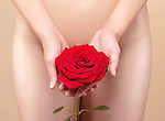 Nude woman holding a red rose in front of her naked body. Womens health concept.