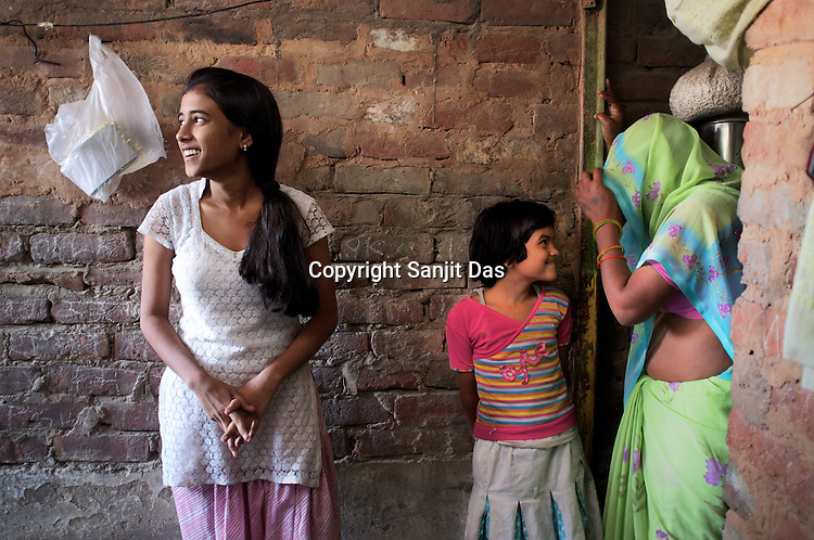 14 year old Bharti's looks on while her youngest sister Pooja shares a light moment with their mother outside on the terrace of their two room apartment in the urban village in Chattarpur, New Delhi, India.