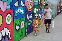 A man looks at his cell phone while walking his dog by murals on the walls in the Bushwick neighborhood of Brooklyn in New York on Saturday, July 27, 2013. The neighborhood is undergoing gentrification changing from a rough and tumble mix of Hispanic and industrial to a haven for hipsters, forcing many of the long-time residents out because of rising rents. (© Frances M. Roberts)