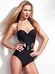 Beautiful young woman wearing a trendy black one-piece monokini swimsuit isolated on white wall background