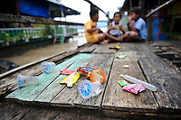 Plastic waste and rubbish left by the shore of a lake, nr Makassar, Sulawesi, Indonesia.