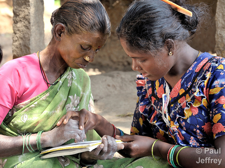 Angali (right) helps Kaniamma with writing during a women's literacy class in Nandambakkam, a tribal village in the southern India state of Tamil Nadu.