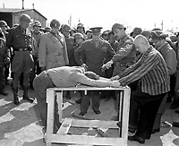 Gen. Dwight D. Eisenhower watches grimly while occupants of a German concentration camp at Gotha demonstrate how they were tortured by the Nazi sadists operating the camp.  Generals Bradley and Patton are at his right.  Germany, April 12, 1945.  Lt. Moore.  (Army)<br /> NARA FILE #:  111-SC-203475<br /> WAR &amp; CONFLICT BOOK #:  1113