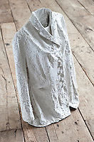 Close up of a jacket made of plaster standing on a rough wooden floor