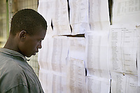 Kenya. Rift Valley province. Nakuru. 25.01.2008. A black Kikuyu man reads the names on various Civil list (paper sheets) taped on an office's wall at Show Ground. The man is an Internally displaced persons (IDPs) forced to flee his home because of the inter-ethnic strife, but who, unlike refugees, remain within his country's borders. The Kikuyus are Kenya's most populous ethnic group.  © 2008 Didier Ruef