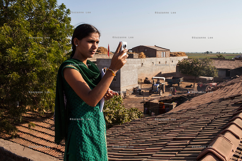 Video Volunteer videojournalist Niru J. Rathod, 24, shoots an overview of a remote village to fit into her documentaries on topics of caste discrimination and water quality issues in a remote village in Surendranagar, Gujarat, India on 14 December 2012. Niru, the 8th child in a family of 11 girls born to a Dalit construction worker, has been using videography for social change since 2006. She shoots and produces her own short documentaries and is a committed video activist, having conducted hundreds of village video screenings where she also speaks to thousands of men, shattering their ideas about what a woman and a Dalit can do while bringing massive changes to the communities she documents. Photo by Suzanne Lee / Marie Claire France