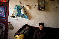 Wang Shou Ha stands inside her home in Fanzhuang Village, Gangyun County, Jiangsu, China, where she and husband Fan Xi Bao care for their orphaned granddaughter Fan Li Na, 10.  The girl's father died in a car crash in 2000 and the girl's mother remarried, abandoning the girl.  Both grandparents are over 60 and have health problems which make it impossible to support the girl if she continues school.  ..At the time of the picture, China's Amity Foundation charity, was investigating the family's situation in preparation to raise money to financially support these children and other orphans in similar situations.  With Amity's support, each orphan, aged 6-12, would receive approximately 1,400 RMB annually (about 200 USD) to pay for the cost of living. Amity works to keep children out of the institutional orphanages in China, preferring to provide monetary assistance that can help maintain a family environment for the orphans it helps.
