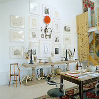 The double-height ceiling creates the ideal space for displaying works of art and a large collection of black-and-white prints and photographs can be seen hanging above an antique French fabric cutter's table