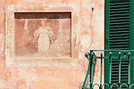 A faded fresco next to an iron green balcony in Griante, a town on Lake Como, Italy.